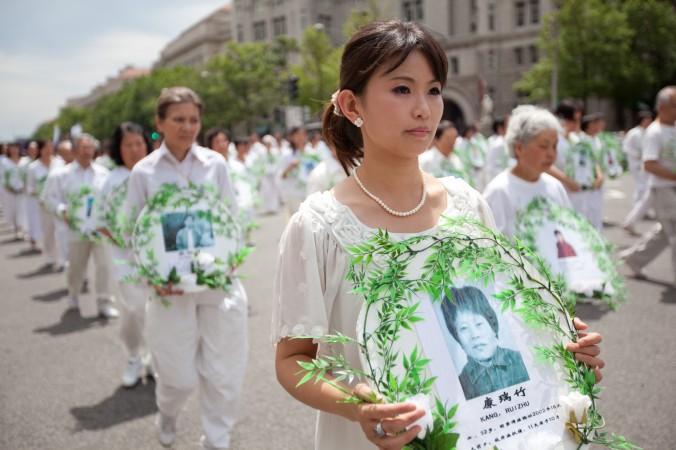 تمرینکنندگان فالوندافا عکسهای برخی قربانیان آزار و شکنجه در چین را در دست دارند