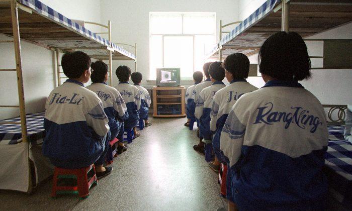 تمرینکنندگان فالون دافا در اردوگاه کار اجباری ماسانجیا مجبور به تماشای فیلمی با محتوای «بازآموزی» هستند. (۲۲ می ۲۰۰۱).  یکی از شنجههای دردناک و متداول در زندانها و این اردوگاه های کار اجباری این است که به دستان آنها را بوسیله دستبند به دو تخت خواب میبندند و سپس تختخواب ها را به دو سمت مخالف هل میدهند.  (AP Photo/John Leicester)