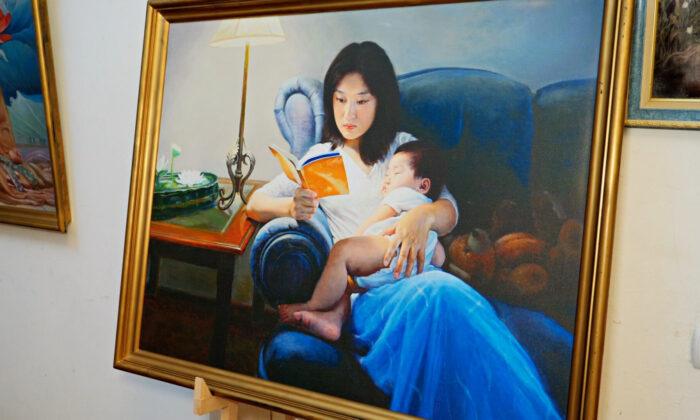 نقاشی زنی که کودک خود را در آغوش گرفته و در حال خواندن کتاب « جوآن فالون » است. ( Screenshot/NTD )