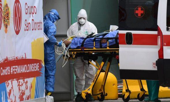 پرسنل پزشکی در روز ۲۳ مارس ۲۰۲۰، بیماری را از آمبولانس صلیب سرخ ایتالیا به بخش مراقبتهای ویژه در یک مرکز ورزشی بیرون از بیمارستان سان رافائل شهر میلان منتقل میکنند. (Miguel Medina/AFP via Getty Images)